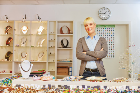 stores: Glimlachende vrouw als winkelbediende achter balie in een juwelierszaak