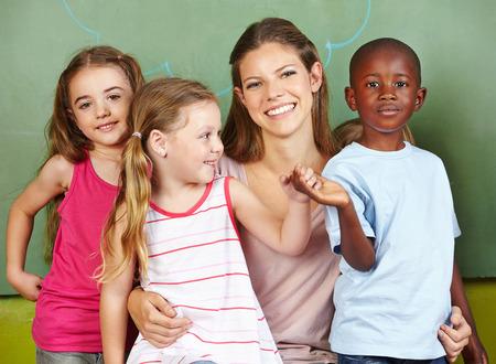 Happy woman with three different children in a kindergarten photo
