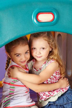 playschool: Two befriended girls embracing in a kindergarten