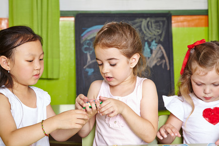 Three girls in a kindergarten playing with building blocks photo
