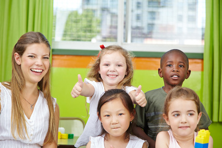 consent: Happy girl in kindergarten group with teacher holding her thumbs up