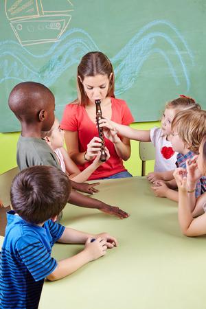 flauta dulce: Profesor del cuarto de niños tocando la flauta para los niños en un jardín de infantes