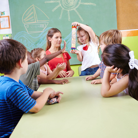 day care center: Preschool musical education with group of children and rainmaker