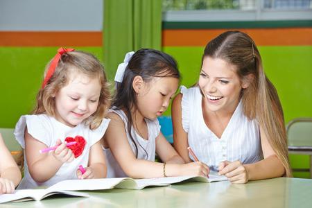 playschool: Kids having fun drawing in kindergarten with a nursery teacher