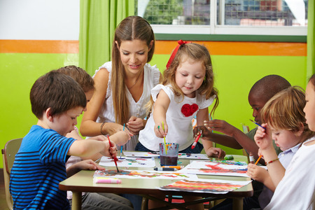 infant school: Many children painting together with nursery teacher in a kindergarten