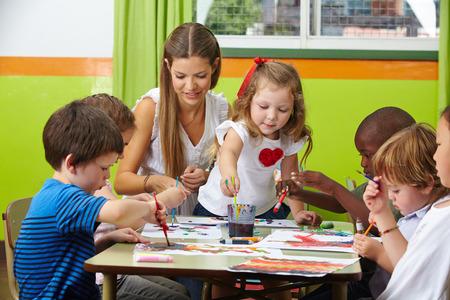 Muchos niños pintando junto con el maestro vivero en un jardín de infantes Foto de archivo