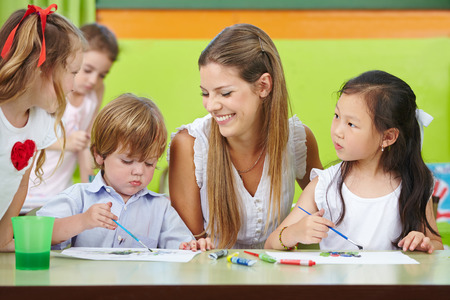 Children are creative painting in kindergarten with a happy nursery teacher