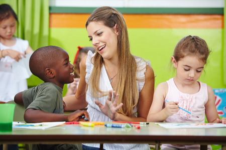 day care: Smiling nursery teacher talking to african boy in kindergarten