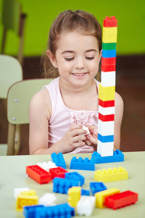 Happy girl playing with colorful building blocks in a nursery room photo