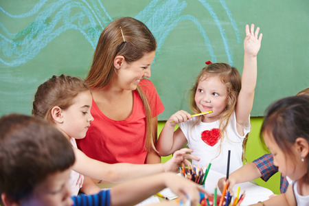 Meisje verhoging van haar hand in de kleuterschool met het schilderen van een foto