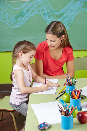 educators: Muchacha que aprende escribir en la clase de preescolar con el maestro de guardería