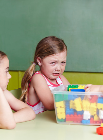 controversy: Sad girl crying in a kindergarten group Stock Photo