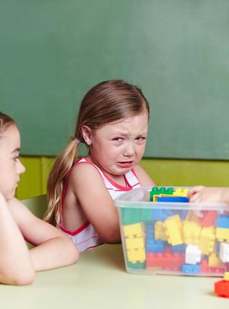 Trauriges Mädchen weinen in einer Kindergartengruppe