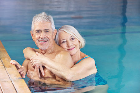 Happy couple senior people bathing in a swimming pool photo