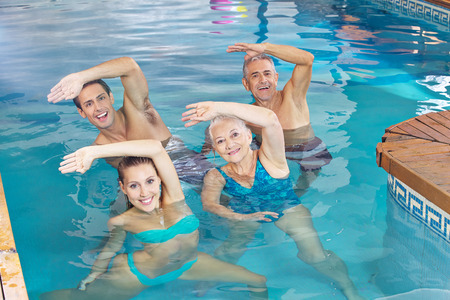 Happy group doing aqua fitness class in a swimming pool photo