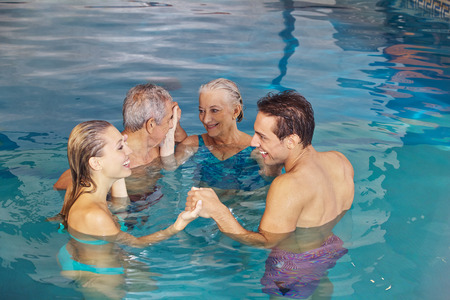 Family with senior couple creating circle in water of swimming pool photo