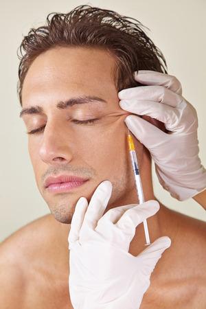 usunięta: Człowiek o kurze łapki usuwa się w klinice piękności z kwasem hialuronowym