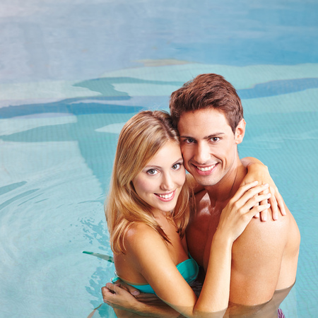 Happy young couple embracing in swimming pool in their holidays photo