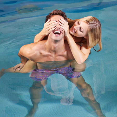togther: Happy young couple having fun togther in swimming pool in summer