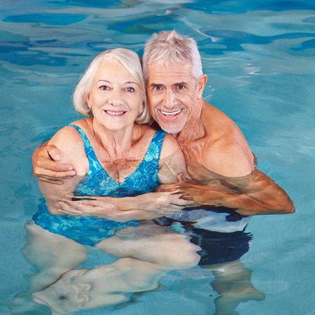 Happy senior couple swimming in hotel pool in summer