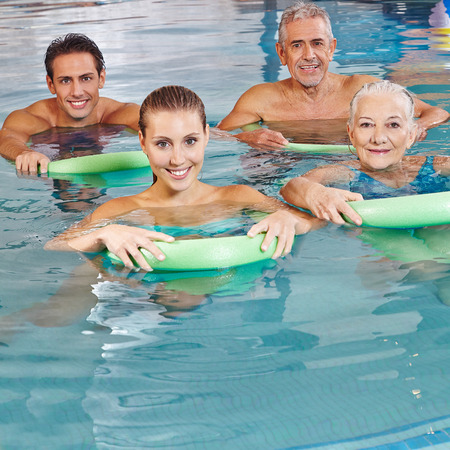 Happy group doing together aqua fitness in swimming pool with swim noodles