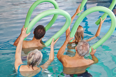hydrotherapy: Group of senior people doing aqua fitness from behind with swim noodles Stock Photo