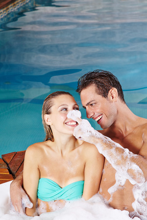 couple having fun: Happy young couple having fun in whirlpool with bubble foam bath