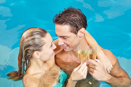 Happy couple in swimming pool toasting with glass of champagne photo