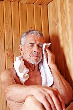 스파 호텔의 사우나에서 수건 땀과 늙은 남자