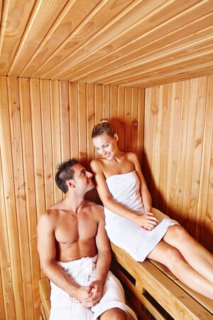 Happy couple relaxing together in sauna of health resort spa photo