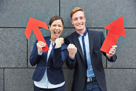 Two happy business people cheering with big red arrows pointing up photo
