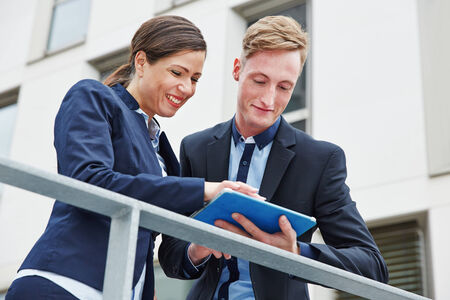 Two happy business people working with tablet computer outside in the city photo