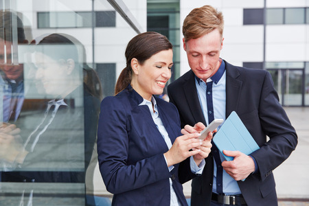 Two business people looking together at smartphone in the city photo