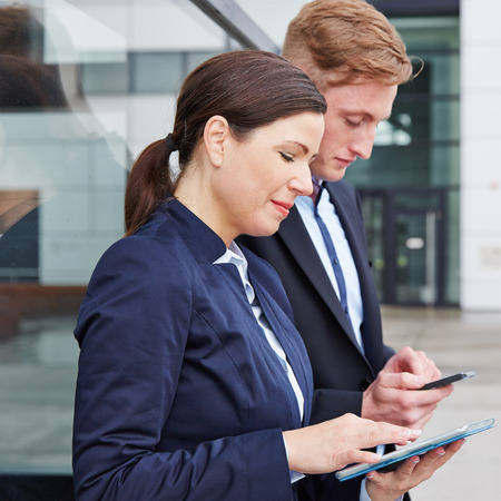 Two business people working with smartphone and tablet PC in front of their office photo