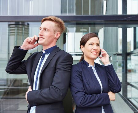Two happy business people in front of office making calls with their smartphone photo