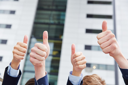 many hands: Cheering business people holding their thumbs up in front of an office