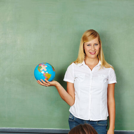 stay on course: Happy teacher holding a globe in elementary school class