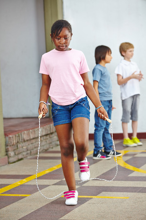 day of school: Girl jumping with skipping rope on schoolyard in elementary school