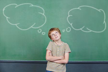 toma de decisiones: Niño de tomar una decisión en la escuela delante de la pizarra con burbujas de pensamiento