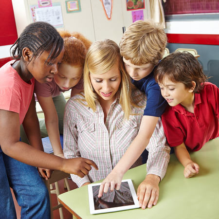 child school: Students and teacher using tablet computer in class in elementary school Stock Photo