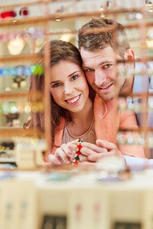 Smiling couple buying a bracelet in a jewelry store photo