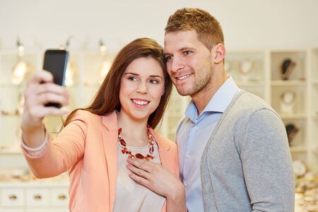 Happy couple taking a selfie photo with smartphone in a jewelry store photo