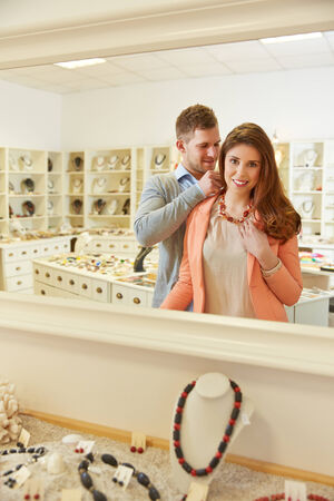 Woman trying on necklace with mirror in a jewelry store photo