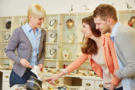 sell: Woman talking to a salesperson at jeweler store Stock Photo