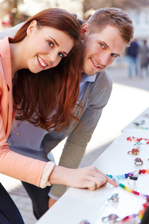 Man and woman looking at jewelry on display at jeweler store photo