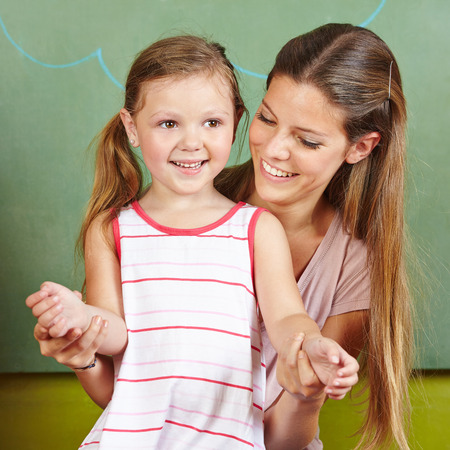 Happy mother with smiling daughter in front of a chalkboard Stock Photo