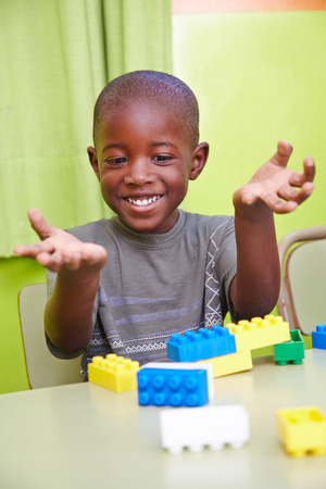 Happy african boy playing in kindergarten with building blocks Stock Photo