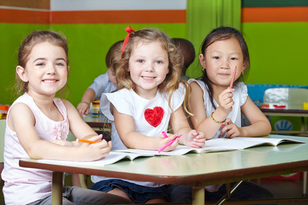 infant school: Many happy children drawing in kindergarten with pens and coloring books