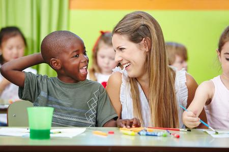 maestra preescolar: Profesor del cuarto de niños y niños que se divierten juntos en un grupo de jardín de infantes