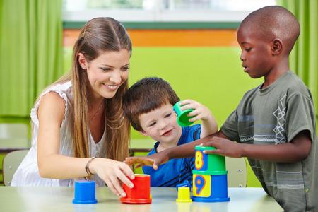 Nursery teacher building tower with children in a kindergarten photo